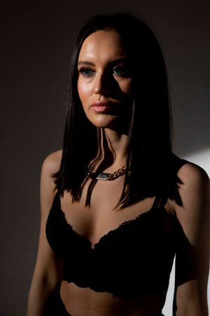 Studio photo of pretty brunette woman in twilight in bra looks into the distance