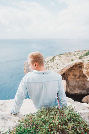 A man seating in front of a large rock. Watching to the sea. Nice weather. High quality photo
