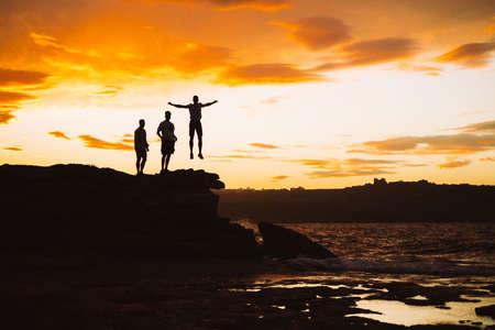 Three people on sunset. Beautiful jump on sunset. Silhouette on the sky. Orange sunset. Malta. Sea view. Фото со стока