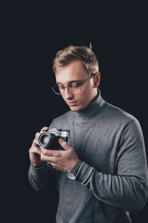 A man holding a camera on black background