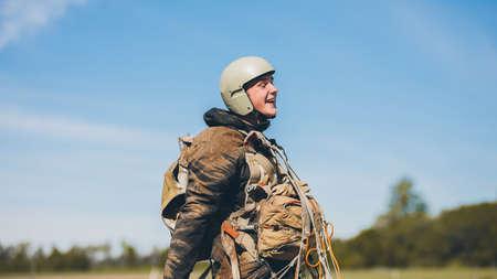 A man wearing a helmet with parachute after landing.