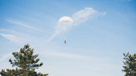 A man flying through the sky with parachute. Blue clean sky.