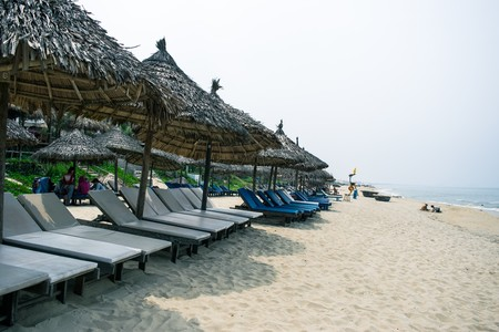 idling: Beach chairs on the white sand beach with cloudy blue sky and sun