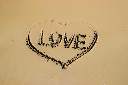 con dao: Word love and shape of heart written on sand at the beach by the sea, symbol of love, summer time
