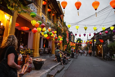 impression: HOI AN, VIETNAM - MARCH 15, 2017: Group of people travel Hoian old town, ancient house, country heritage, city friendly with environment, walk, bicycle or pedicab on street, traveller visit at Vietnam Editorial