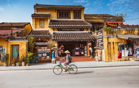 HOI AN, VIETNAM - MARCH 15, 2017: Group of people travel Hoian old town, ancient house, country heritage, city friendly with environment, walk, bicycle or pedicab on street, traveller visit at Vietnam Editöryel