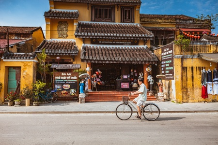 HOI AN, VIETNAM - MARCH 15, 2017: Group of people travel Hoian old town, ancient house, country heritage, city friendly with environment, walk, bicycle or pedicab on street, traveller visit at Vietnam Editorial