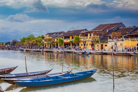 HOI AN, VIETNAM - MARCH 17, 2017: Traditional boats in front of ancient architecture in Hoi An, Vietnam. Hoi An is the Worlds Cultural heritage site, famous for mixed cultures & architecture.