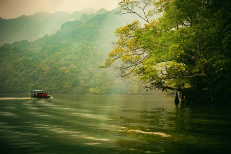Ba Be lake, Bac Kan province, Vietnam - September 22, 2016 : tourists on the boat are going to enjoy and explore Ba Be lake. Stunning scenery of Ba Be Lake in Bac Kan Province, Vietnam Stok Fotoğraf - 82782979