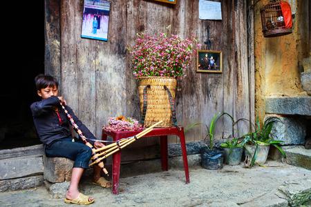 HA GIANG, VIETNAM, November 14th, 2017: Hmong young men playing a traditional instrument, northern Vietnam Editorial
