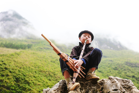 HA GIANG, VIETNAM, el 14 de noviembre de 2017: Hombres jovenes de Hmong que juegan un instrumento tradicional, Vietnam septentrional