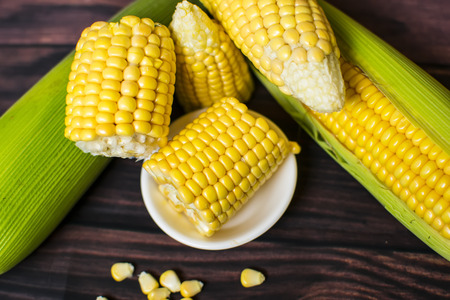 Fresh corn on cobs on wooden table, closeup, top view