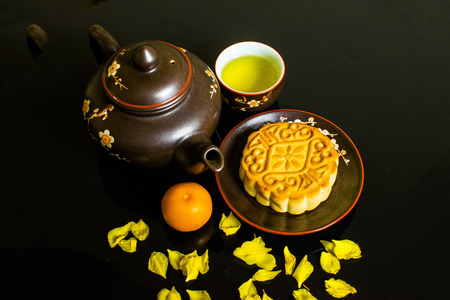 Mooncake and tea, Chinese mid autumn festival food isolated on black background.