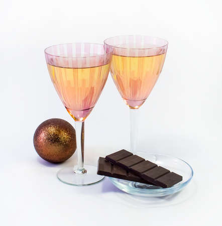 Champagne in two wine glasses, chocolate and jewelry photo