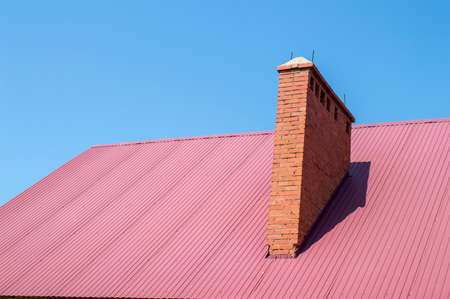 red sky: Brick pipe and roof of red color Stock Photo