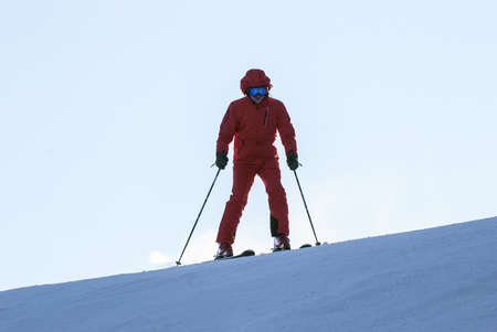 The mountain skier who is climbing down a mountain on the route