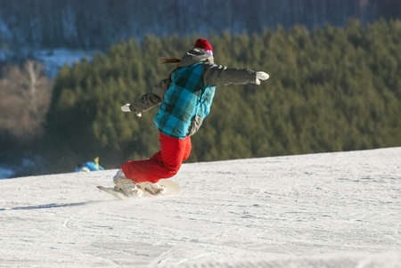 The snowboarder who is climbing down a mountain on the route  Stock Photo