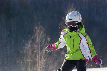 The girl on mountain skiing climbing down a mountain