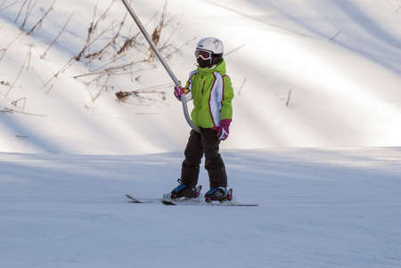 The young skier on the surface lift on the route  Stock Photo