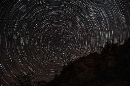 polaris: Star trails at night upon rocks with full circle around Polaris