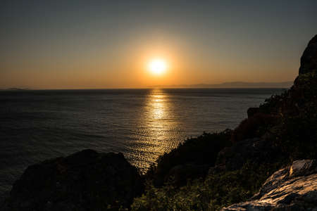 aegean: Sunset behind rocky foreground in aegean sea Stock Photo