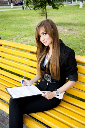 young girl sits in park on a bench with tablet photo