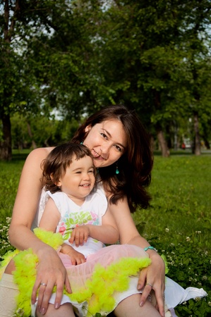 Mum embraces the daughter, sitting on the grass photo