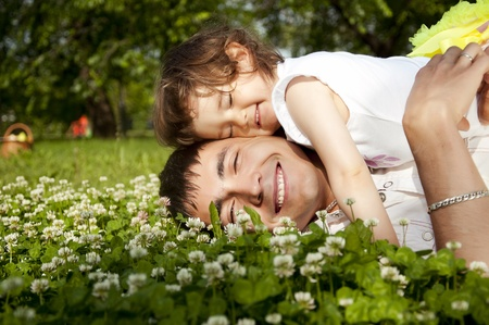 dad daughter: The father and the daughter together lay on a grass