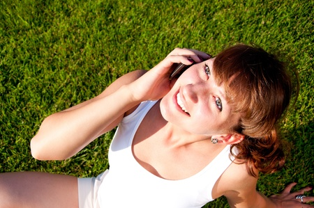 portrait of young woman talking on phone, green grass background Stock Photo - 9910332