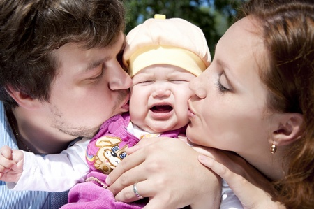 Father and mother kissing a child, the child is crying and sad photo