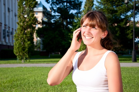 portrait of young woman talking on phone, green grass background Stock Photo - 9910336