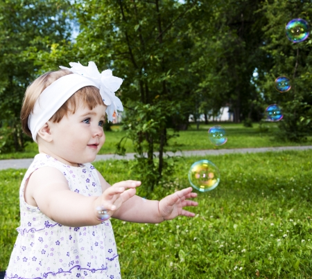 Portrait of the girl playing with soap bubbles photo