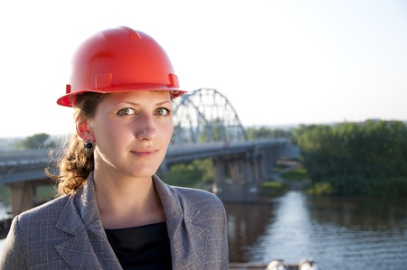 Young architect-woman wearing a protective helmet standing on the bridge background is smiling photo