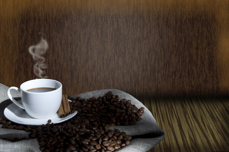 cup of coffee and coffee beans on the Sacking, abstract grunge background