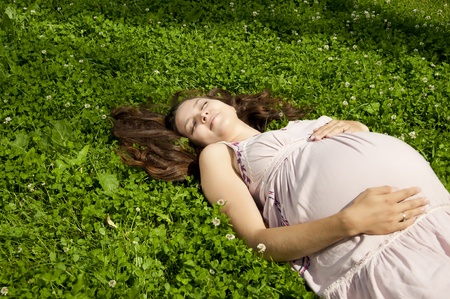Beautiful pregnant woman relaxing in the summer park Stock Photo
