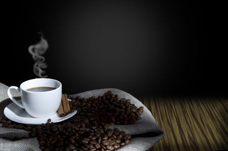 coffe break: cup of coffee and coffee beans on the Sacking, abstract grunge background