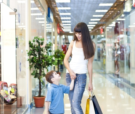 retail place: Mum and the son discuss purchases in shopping center