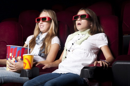 two girls look three-dimensional cinema, sitting in the glasses, eat popcorn, drink drink Stock Photo - 10463957