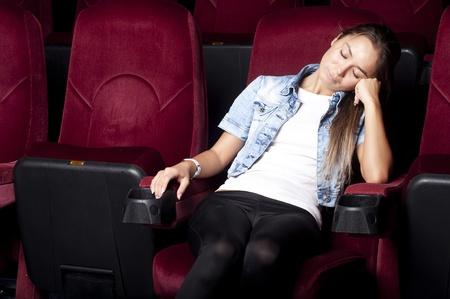 young beatiful woman asleep in the cinema photo
