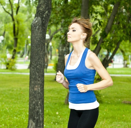 young woman jogging in the park in summer, trees and grass background Stock Photo - 10579716