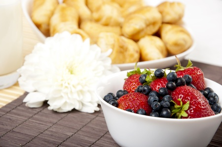 light Breakfast: cold milk, croissants and Berries on a table photo