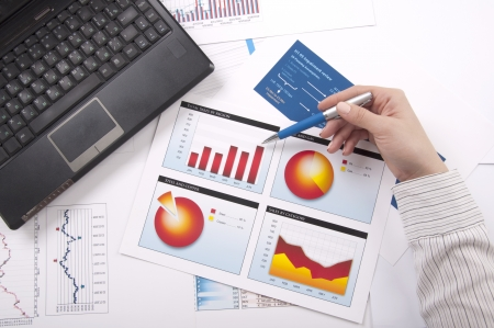 analisys: The hand specifies the financial chart, a workplace Stock Photo