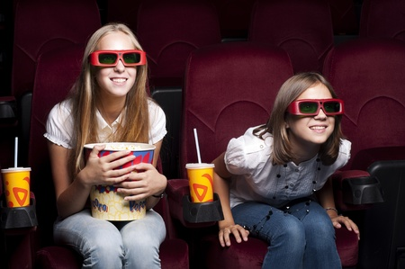 theater seat: two girls look three-dimensional cinema, sitting in the glasses, eat popcorn, drink drink
