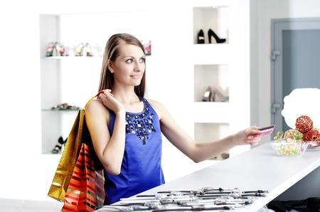 Young woman at shopping mall checkout counter paying through credit card Stock Photo - 11746621