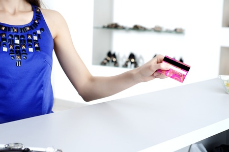 Young woman at shopping mall checkout counter paying through credit card Stock Photo - 11746604