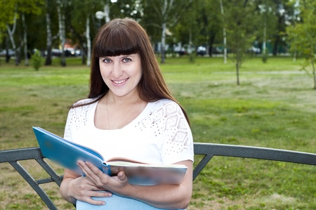 Young beautiful pregnant woman read book on the desk photo
