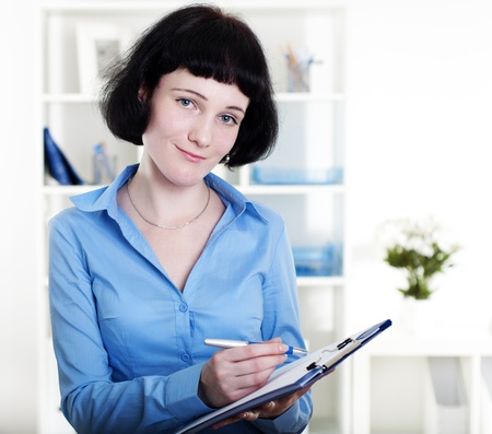 Portrait of a business woman in the office doing some paperwork Stock Photo - 12328182