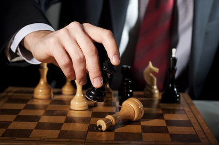 image of the businessman in a business suit plays chess photo