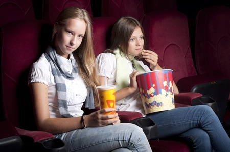 two girls look three-dimensional cinema, sitting in the glasses, eat popcorn, drink drink photo