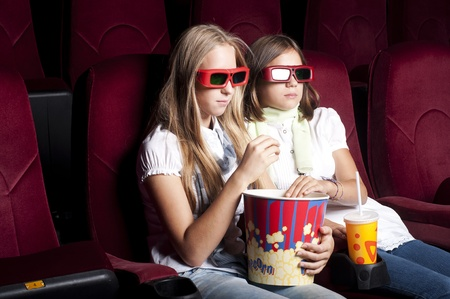 two girls look three-dimensional cinema, sitting in the glasses, eat popcorn, drink drink Stock Photo - 12381663